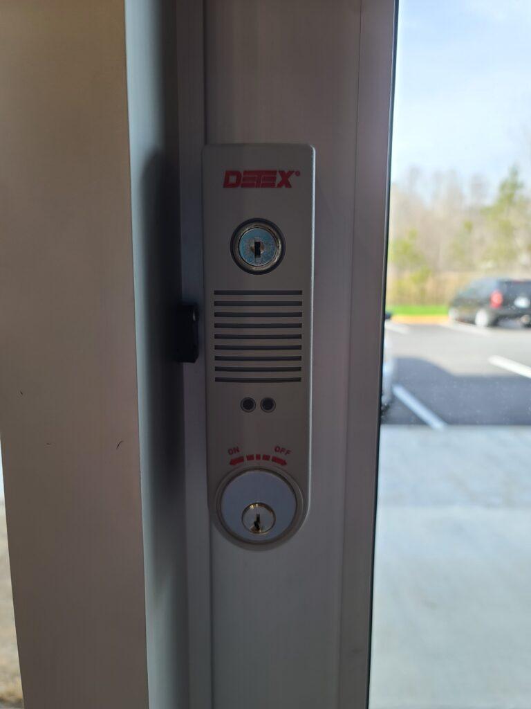 Door alarms by Detex installed on a commercial door.